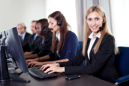 sales call: Closeup portrait of pretty customer care operator with colleagues sitting in a row in background Stock Photo