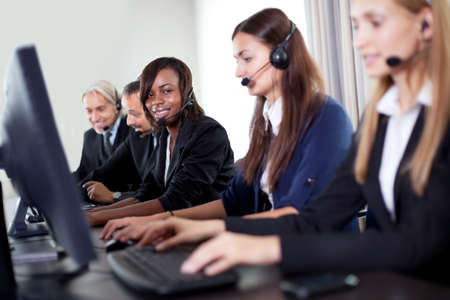 Closeup of beautiful customer service woman with team in background Stock Photo - 11080041