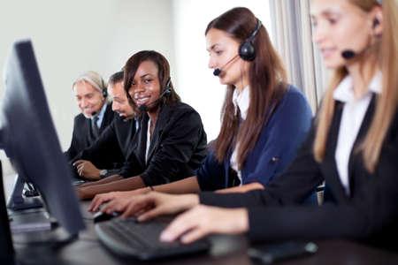 gl�cklicher kunde: Nahaufnahme der sch�nen Frau mit Kundenservice-Team im Hintergrund