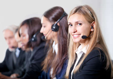 call center agent: How can I help you? Closeup portrait of beautiful young female customer service representative with colleagues Stock Photo