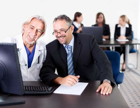 Mature male doctor showing patient prescription on his computer - Colleagues in the background photo