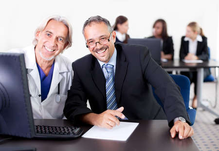 medical office: Happy male doctor discussing with patient at his clinic - colleagues in the background