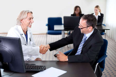 office staff: Mature doctor smiling and shaking hands with a patient at his desk in his office - colleagues in the background