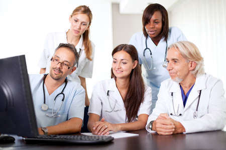 medical career: Friendly group of doctors at the hospital looking at a computer