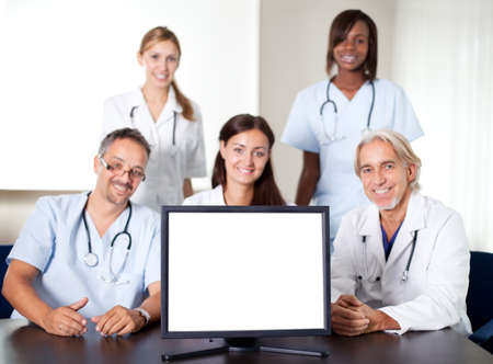 Closeup portrait of doctors and nurses in a meeting with a monitor in the foreground photo
