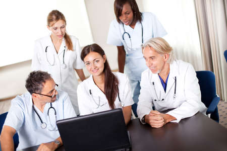 Portrait of mature young doctors working together looking at laptop in a meeting room photo