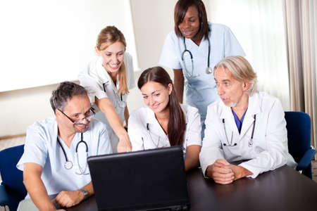 Portrait of group of smiling hospital colleagues looking at the laptop and discussing Stock Photo - 11080333