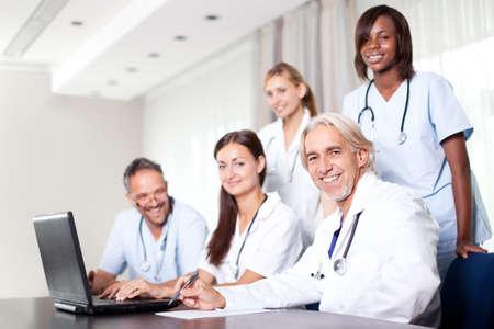 Office uniforms: Atractiva mujer m�dico que trabaja en su computadora port�til con los colegas de la salud en su oficina Foto de archivo
