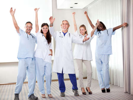 Group of happy doctors smiling and waving after a successful surgey at a hospital photo