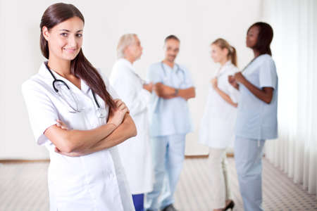 folded hands: Friendly female doctor with folded hands smiling at the camera with colleagues discussing in the background Stock Photo