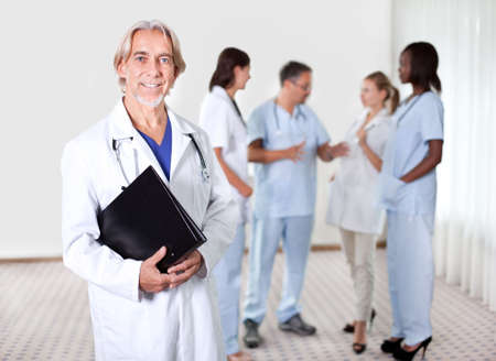 Mature doctor holding files with a group of doctors discussing behind photo