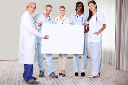 Happy confident group of doctors holding a blank placard pointing towards copy space photo