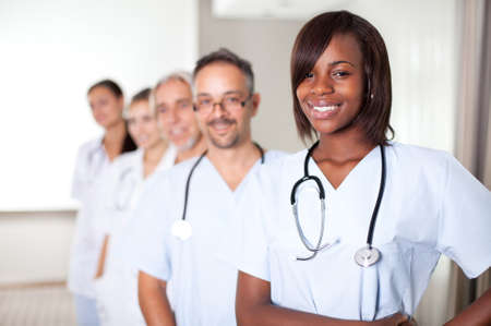 healthcare workers: Multi-ethnic team of confident happy doctors standing in a row at the hospital