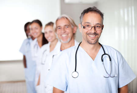 hospital staff: Portrait of a mature male doctor standing in front of his team and smiling Stock Photo