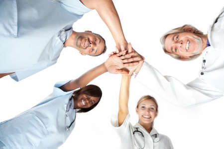 Group of doctors joining hands with low angle view � Isolated on white background photo