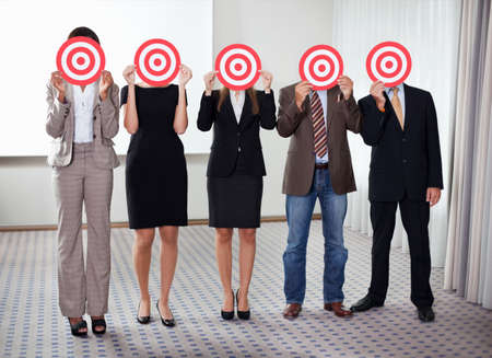 Group of business people holding a target against their faces.