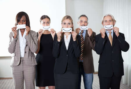 Multiethnic group of people holding card of smile by their mouth. photo