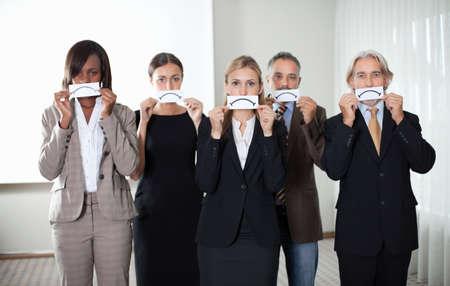 Diverse groep mensen uit het bedrijfsleven met een kaart met droevig teken door hun gezichten.
