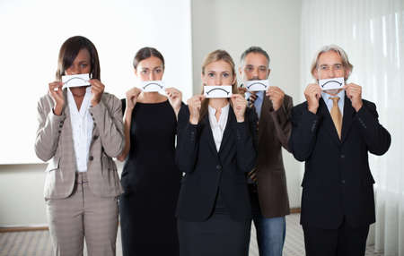 diverse hands: Diverse group of business people holding a card with sad sign by their faces. Stock Photo