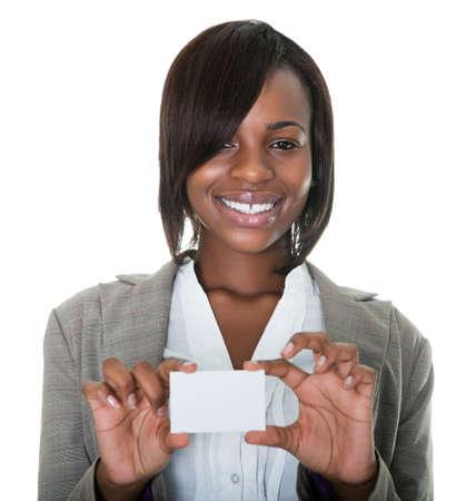 mujeres africanas: Retrato de joven empresaria afroamericana, que sostiene la tarjeta en blanco sobre fondo blanco. Foto de archivo
