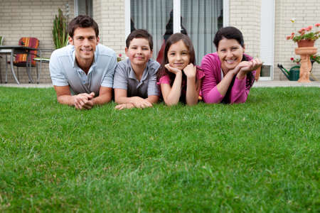 Young father and mother with their kids lying on grass in their backyard photo