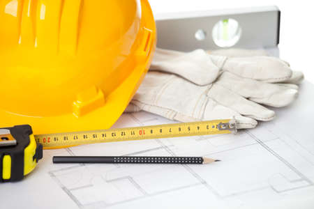 building plans: Hardhat gloves and measuring instruments on blueprint Stock Photo