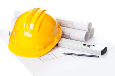Image of  blueprints with level pencil and hard hat on table photo