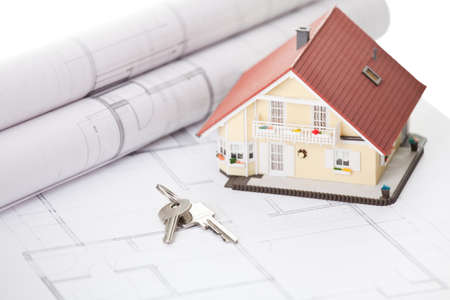 Model home and house key on architectural floor plans photo