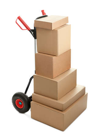 Large dolly with brown shipping boxes isolated on white background photo