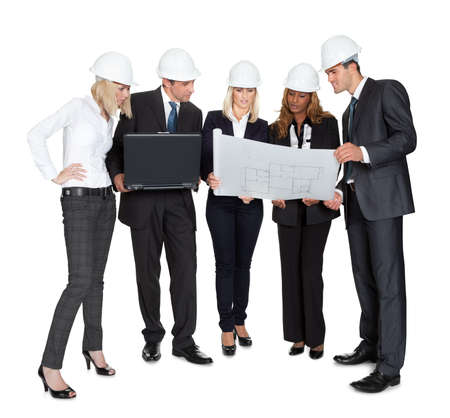 Team of confident architects studying blueprints on white background photo
