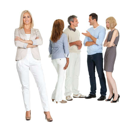 business woman standing: Portrait of confident young lady with group of people talking in background Stock Photo