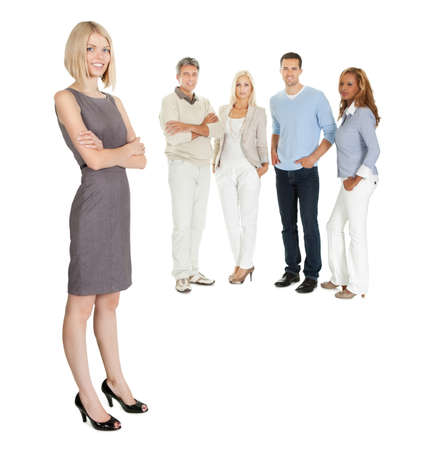 Pretty business woman standing with colleagues at the back on white photo