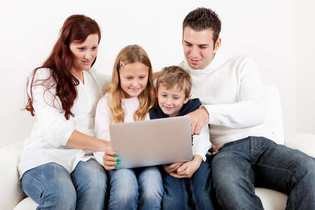 buying online: Happy family spending time together and using laptop at home