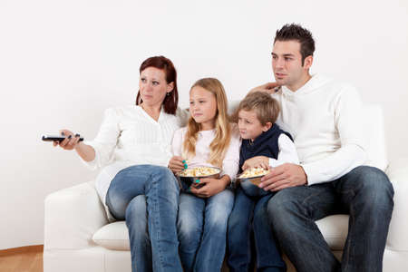 cheeful: Cheeful young family watching TV together at home Stock Photo