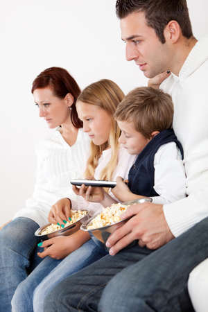 Cheeful young family watching TV together at home photo