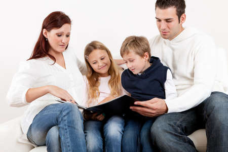 Hapy young family watching photo album at home Stock Photo