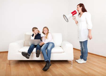 Outrageous moeder schreeuwen tegen kinderen met een laptop met behulp van megafoon Stockfoto