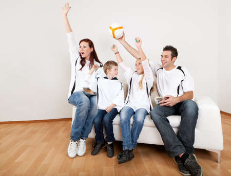 Young family cheering after goal during football match at home photo