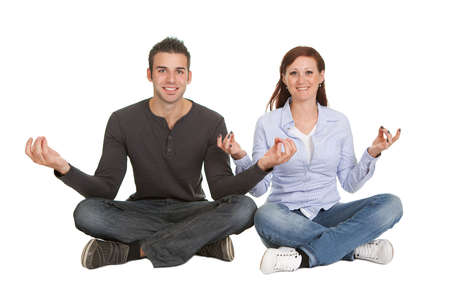 Cheeful young couple doing yoga exercise. Isolated on white photo