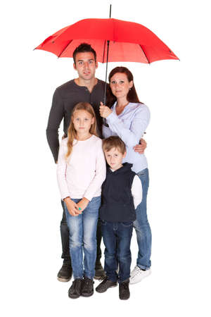 red umbrella: Happy young family using umbrella. Isolated on white Stock Photo