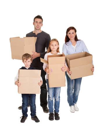 cajas de carton: Joven familia feliz llevando cajas de cart�n aislado en blanco Foto de archivo