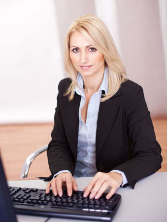 Beautiful businesswoman working on computer in the office photo