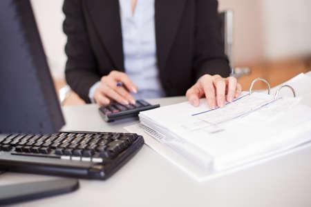 impuestos: Primer plano de una mujer de negocios haciendo las finanzas en la oficina