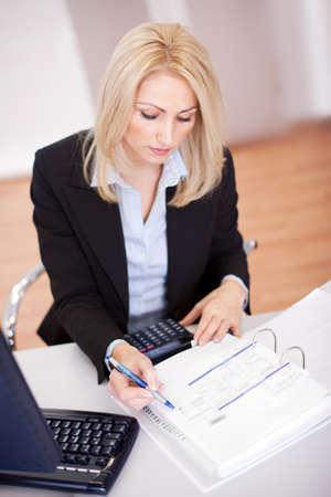 expert comptable: Belle femme d'affaires faisant des finances dans le bureau Banque d'images