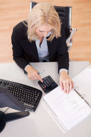 tax consultants: Beautiful businesswoman doing finances in the office Stock Photo