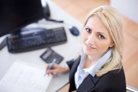 Beautiful businesswoman doing finances in the office photo