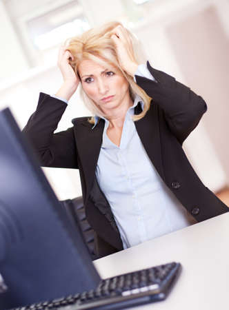 Stressful business woman working on computer at the office photo