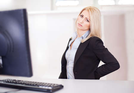 Business women having back pain at computer workplace photo