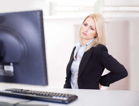 woman pain: Business women having back pain at computer workplace