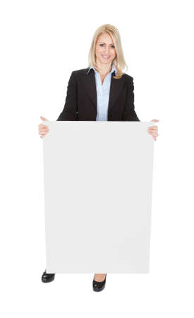 Cheerful businesswomen presenting empty board. Isolated on white photo